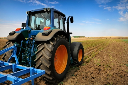 farm machinery: The Tractor - modern farm equipment in field  Stock Photo