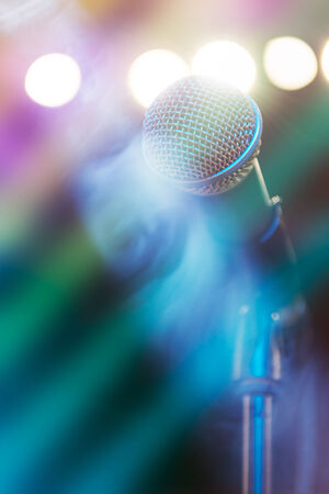 stage lighting: Microphone on stage with shiny rays as the background Stock Photo
