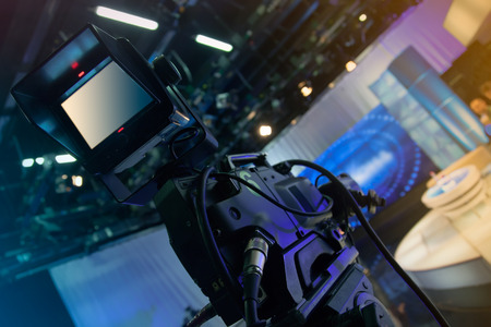 tv sets: Television studio with camera and lights - recording TV show. Shallow depth of field - focus on camera Stock Photo