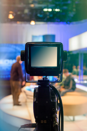 breaking news: Television studio with camera and lights - recording TV show. Shallow depth of field - focus on camera Stock Photo