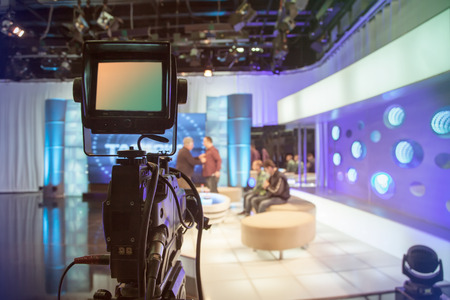 channel: Television studio with camera and lights - recording TV show. Shallow depth of field - focus on camera Editorial