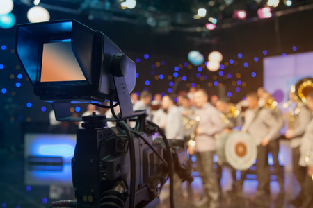 Television studio with camera and lights - recording TV show. Shallow depth of field - focus on camera Stock Photo