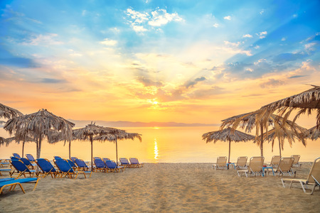 beautiful umbrella: Vivid sunrise on a beautiful sandy beach with sunshade Stock Photo
