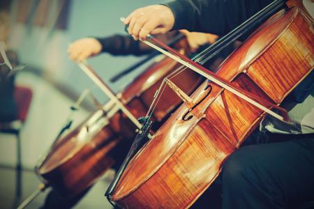 violines: Orquesta Sinfónica en el escenario, manos tocando el violoncelo Foto de archivo