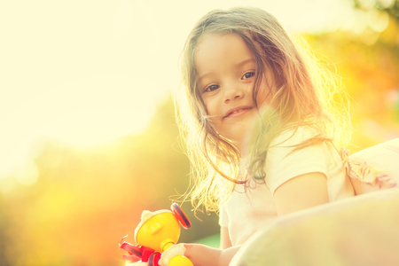 smile girl: Smiling little girl with toy in hands. Portrait in nature with warm sunlight. Shallow depth of field. Selective focus.