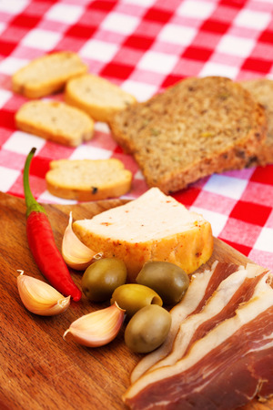 Traditional mediterranean food with ham, olives, hot peppers and bread. Stock Photo