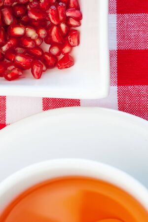 Fresh antioxidant pomegranate tea in the white cup.