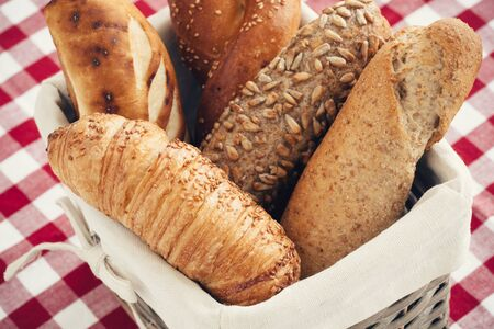 french bread: Various kinds of fresh tasty bread in wicker basket. Shallow depth of field, vintage style. Stock Photo