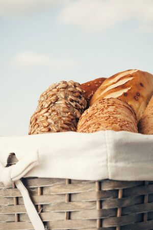 kinds: Various kinds of fresh tasty bread in wicker basket. Shallow depth of field, vintage style. Stock Photo