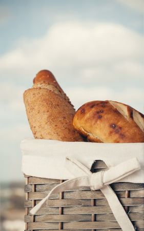 basket: Various kinds of fresh tasty bread in wicker basket. Shallow depth of field, vintage style. Stock Photo
