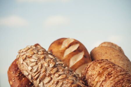 Various kinds of fresh tasty bread in wicker basket. Shallow depth of field, vintage style. Stock Photo