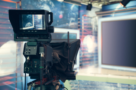 spot: Television studio with camera and lights - recording TV NEWS. Shallow depth of field - focus on camera.