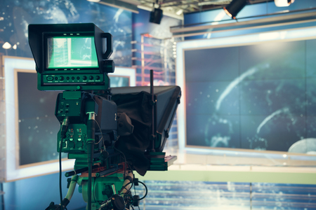 studio: Television studio with camera and lights - recording TV NEWS. Shallow depth of field - focus on camera.