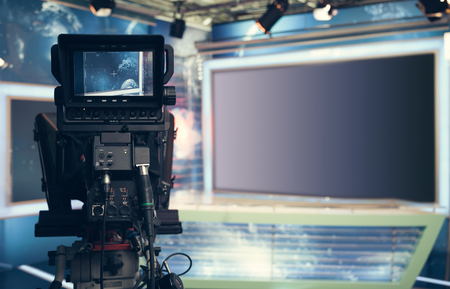 studios: Television studio with camera and lights - recording TV NEWS. Shallow depth of field - focus on camera.