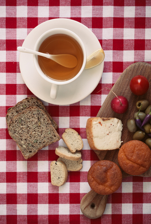 Breakfast with  bread, tomato, radish, olives, peppers, cheese and tea.