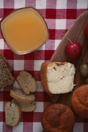 Breakfast with bread, radish, olives, cheese and juice.