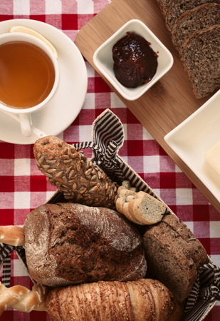 Breakfast with healthy brown bread, black tea, butter and preserved jam.
