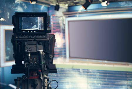 camera: Television studio with camera and lights - recording TV NEWS. Shallow depth of field - focus on camera.