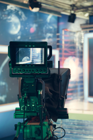 broadcast: Television studio with camera and lights - recording TV NEWS. Shallow depth of field - focus on camera.