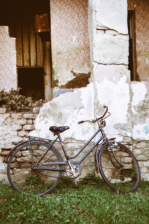 Old bike parked at the farmhouse. Rustic rural scene.
