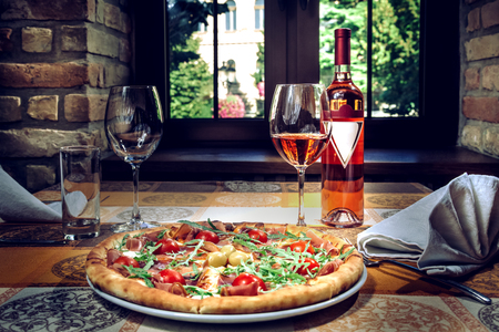 Pizza and red wine on the table. Restaurant ambiente.