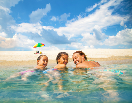 Mom and daughter swim in the shallow sea. They laugh and enjoy on a beautiful beach.