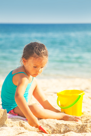 Children on the beach. Beautiful little girl are playing on the sand by the sea. Stock Photo