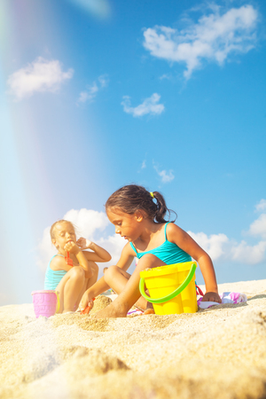 Children on the beach. Beautiful little girls are playing on the sand by the sea. Stock Photo