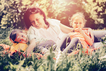 Mother and daughters in the park. They sit on the grass, laugh and enjoy their free time.