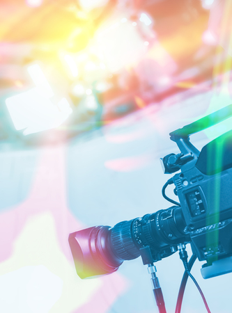 Television studio with camera and lights - recording TV NEWS. Shallow depth of field - focus on camera.