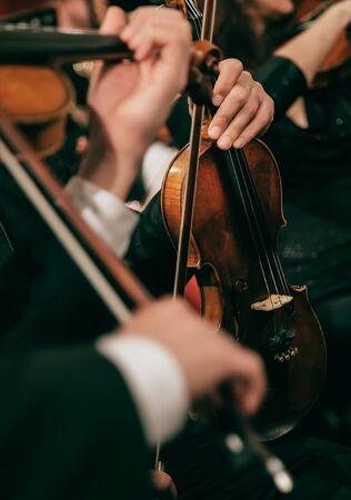 Orquesta sinfónica en el escenario, manos tocando el violín Foto de archivo