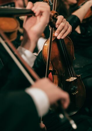 Symphony orchestra on stage, hands playing violin