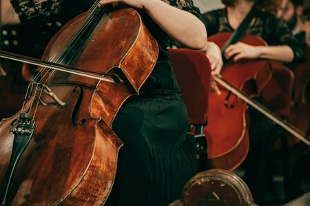 Symphony orchestra on stage, hands playing cello Stock Photo