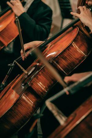 Orquesta sinfónica en el escenario, manos tocando el violonchelo