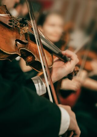 Orquesta sinfónica en el escenario, manos tocando el violín