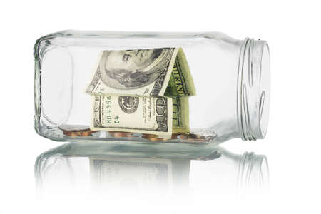 money jar: Savings and investment - Money house and coins in glass jar on white background