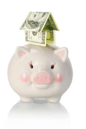 Investment priority - Money house piggyback on piggy bank on white background photo