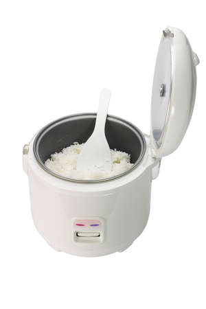 Cooked rice in electric cooker with plastic spoon on white background