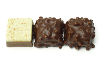 Row of three chocolate cubes on white background photo