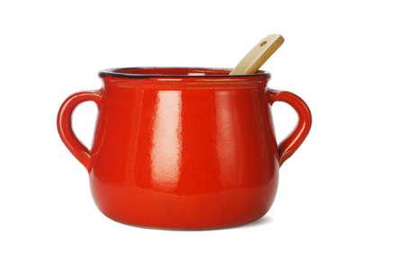 Rode klei pot met houten pollepel op witte achtergrond