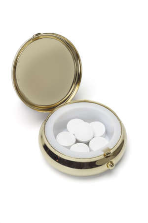 Medicine in round metal pill container on white background photo