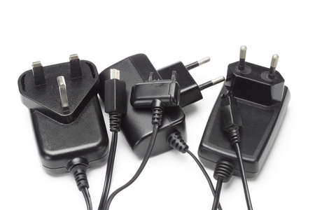 charging: Assorted mobile phone chargers and adapters on white background Stock Photo