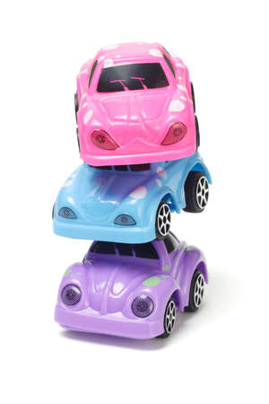 Stack of colorful plastic toy cars on white background photo