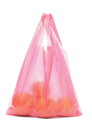 Red plastic bag of oranges on white background photo