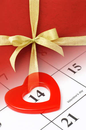 Composite image of gold bow ribbon on calendar page showing Febraury 14 Valentine's day