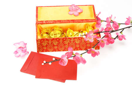 gold ingot: Chinese new year gift box, red packets and ornaments on white background  Stock Photo