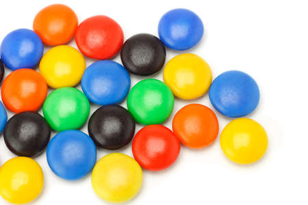 spreaded: Colorful chocolate button candies spreaded randomly on white background