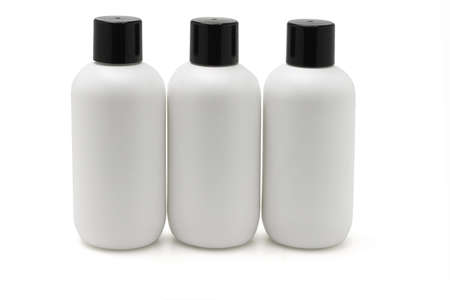 cleanser: Three white plastic bottles arranged in a row on white background