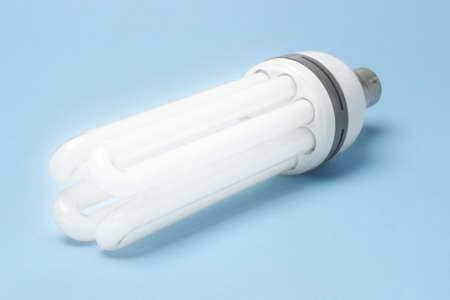 Daylight energy efficient fluorescent lightbulb on blue background photo