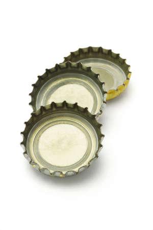 Three bottle caps lying on white background